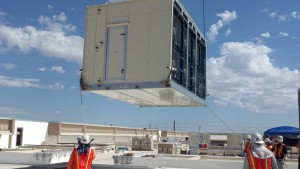 An evaporative cooling unit being lowered into place. (Source: UMP)