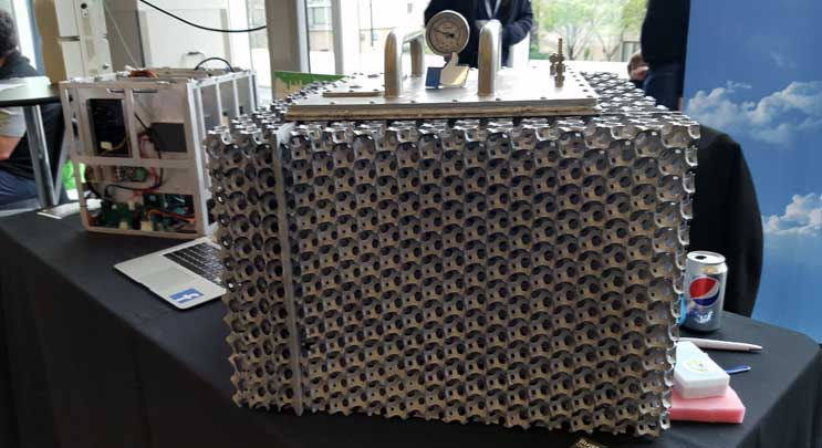 A RuggedPOD enclosure on display at the Open Compute Summit in San Jose, Calif. The sealed cube contains four motherboards immersed in dielectric cooling fluid. (Photo: Rich Miller)