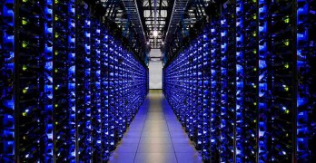 A blue-lit row of servers in a Google data center, (Photo: Google)