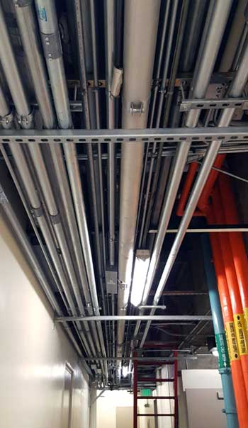 Dense clusters of conduits protecting power and network cabling pack the corridors, risers and stairwells at One Wilshire. (Photo: Rich Miller)