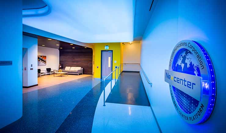 The lounge area at the entrance of the RagingWire VA2 data center in Ashburn, Virginia, featuring the logo for the NTT Nexcenter data center family. (Image: RagingWire)