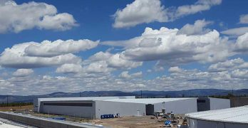 A cloud-filled sky above a Facebook cold storage data center, framed by the mountains of central Oregon. (Photo: Rich Miller)