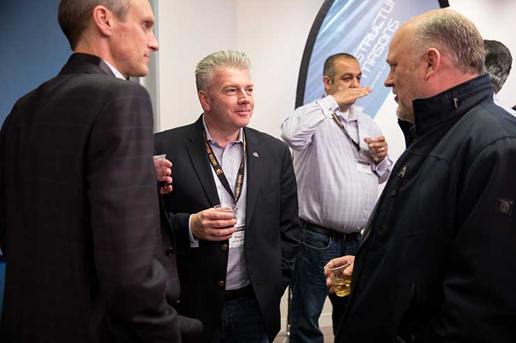 Phill Lawson-Shanks of EdgeConneX (center) talks with Aligned Energy CEO Andrew Schaap (left) and CTO and co-founder Jakob Carnemark. (Photo: Infrastructure Masons)