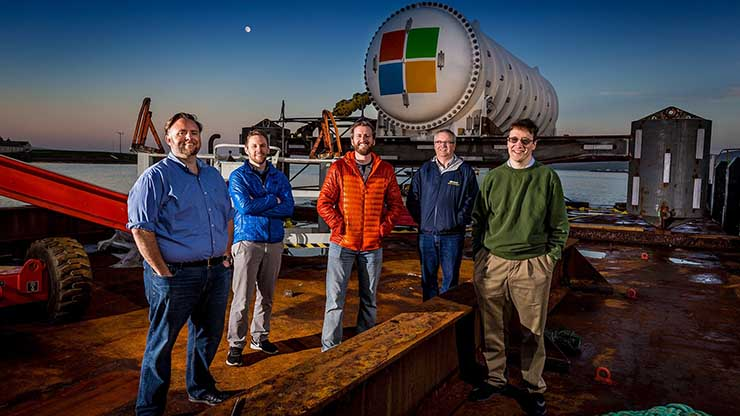 Microsoft's Project Natick team gathers on a barge tied up to a dock in Scotland's Orkney Islands in preparation to deploy the Northern Isles datacenter on the seafloor. Pictured from left to right are Mike Shepperd, senior R&D engineer, Sam Ogden, senior software engineer, Spencer Fowers, senior member of technical staff, Eric Peterson, researcher, and Ben Cutler, project manager.