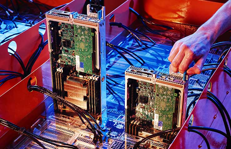 Servers being immersed in coolant fluid in a custom cooling enclosure invented by DownUnder GeoSolutions for high-performance data-crunching for the energy industry. (Photo: DownUnder GeoSolutions)