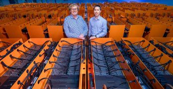 "Dr. Matthew Lamont (left), DownUnder GeoSolutions (DUG) managing director, and Phil Schwan, DUG CTO, stand among the cooling tanks that make up the ""Bubba"" supercomputer at the Houston Skybox data center. (Credit: DownUnder GeoSolutions)"