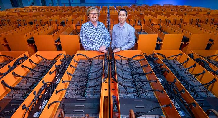 """Dr. Matthew Lamont (left), DownUnder GeoSolutions (DUG) managing director, and Phil Schwan, DUG CTO, stand among the cooling tanks that make up the """"Bubba"""" supercomputer at the Houston Skybox data center. (Credit: DownUnder GeoSolutions)"""