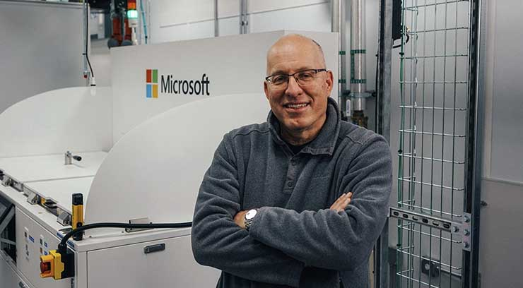 Christian Belady, distinguished engineer and vice president of Microsoft's datacenter advanced development group, stands next to a two-phase immersion cooling tank at a Microsoft data center. (Photo: Microsoft)